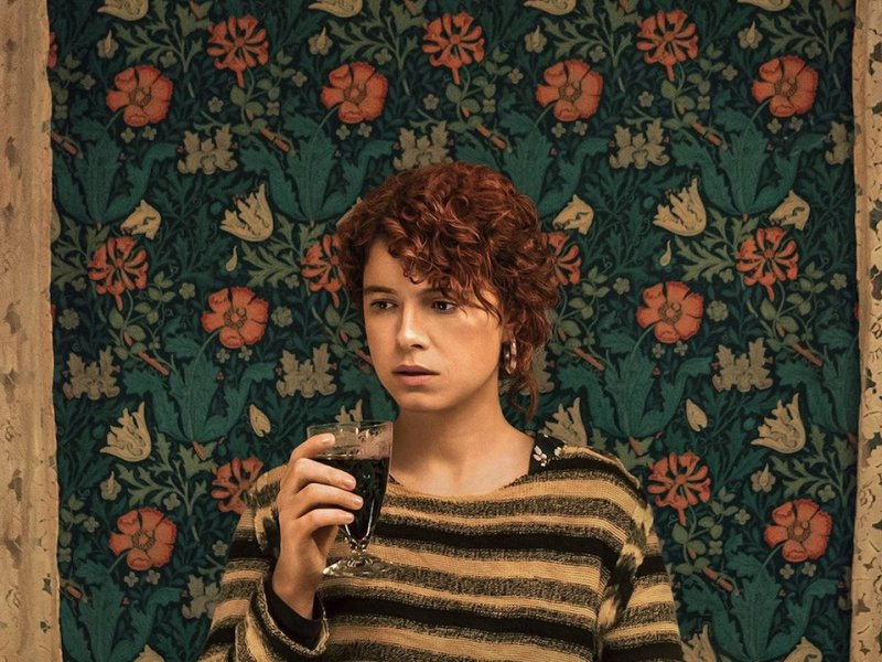 Girl with curly red hair standing in front of a floral background while holding a glass of wine